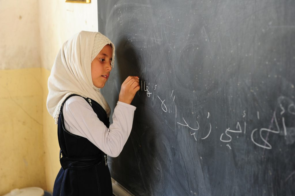 An Iraqi girl writing on a chalkboard